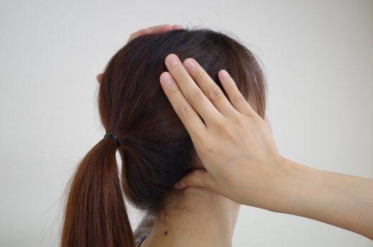 首と頭の境目のストレッチをする女性