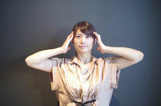 頭部の筋肉ストレッチをする女性